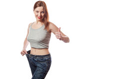 Full-length portrait of attractive slim young smiling woman in big jeans showing successful weight loss with her thumb up, isolate Stock Photo