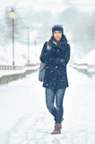 Full length portrait of attractive woman in winter park Royalty Free Stock Image