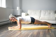 Full length portrait of attractive young woman working out at home in living room, doing yoga or pilates exercise Royalty Free Stock Image