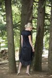 Full length portrait of beautiful barefooted young women wearing black dress while standing under pine tree. Full length portrait of beautiful barefooted young royalty free stock images