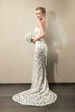 Full length portrait of a beautiful bride holding bouquet. Beautiful bride in elegant white lace wedding dress wearing jewellery. Woman with blond hair, make stock images