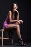 Full-length portrait of beautiful brunette young woman sitting o Stock Images