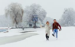 Full-length portrait of the beautiful couple holding hands while happily walking along the village covered with snow. During the snowfall Stock Photos