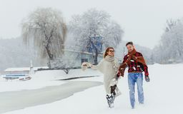 Full-length portrait of the beautiful couple holding hands while happily walking along the village covered with snow. During the snowfall Stock Photo
