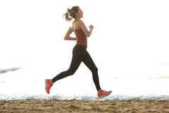 Full length beautiful female jogger on beach for workout routine. Full length portrait of beautiful female jogger on beach for workout routine royalty free stock photo