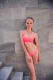 Full-length portrait of beautiful girl in the pink swimsuit with shapely body is posing near the swimming pool on. Mountain resort Royalty Free Stock Photography