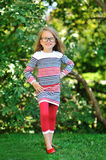 Full length portrait of a beautiful little girl in glasses posin Royalty Free Stock Photos