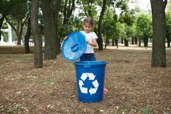 A little cute girl opening a dark blue recycling bin on a blurred natural background. Ecology and children. Royalty Free Stock Image