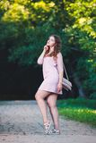 Full length portrait of a beautiful plus size fashion model in pink dress, young woman outdoors Royalty Free Stock Images