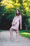 Full length portrait of a beautiful plus size fashion model in pink dress, young woman outdoors Royalty Free Stock Photo