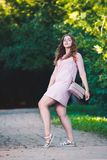Full length portrait of a beautiful plus size fashion model in pink dress, young woman outdoors Stock Photography