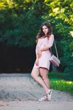 Full length portrait of a beautiful plus size fashion model in pink dress, young woman outdoors Stock Image