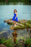 Full length portrait of beautiful sad young brunette woman. Wearing elegant blue dress, standing on a stone river bank reflecting on calm clear  water Royalty Free Stock Photo