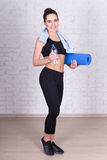 Full length portrait of beautiful sporty woman with yoga mat sta Stock Photography