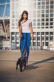 Full length portrait of beautiful woman and black bulldog puppy Royalty Free Stock Photo