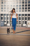 Full length portrait of beautiful woman and black bulldog puppy Royalty Free Stock Images