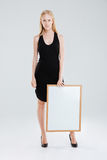 Full length portrait of a beautiful woman holding blank board Royalty Free Stock Photography