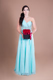 Full length portrait of beautiful woman holding box with red flo Royalty Free Stock Image