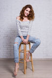 Full length portrait of beautiful woman sitting over white brick Stock Photography