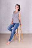 Full length portrait of beautiful woman sitting on wooden chair Stock Images