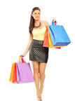 Full length portrait of a beautiful woman walking with shopping Royalty Free Stock Image