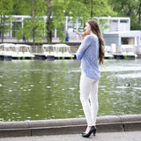 Full length portrait of a beautiful woman in white pants and blu. Happy young woman in white pants and a blue shirt walking in the summer park Royalty Free Stock Photography