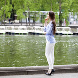 Full length portrait of a beautiful woman in white pants and blu Stock Photos
