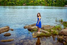 Full length portrait of beautiful young brunette woman. Wearing elegant blue dress, standing on a stone at river bank, reflecting in calm water Stock Photo
