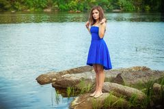 Full length portrait of beautiful young brunette woman. Wearing elegant blue dress, standing on a stone river bank touching her hair Stock Photography