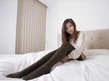 Full length portrait of beautiful young woman in stockings sitting on bed Royalty Free Stock Photo