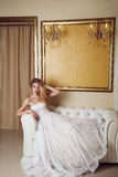 Full length portrait of beauty bride in white dress sitting in s Royalty Free Stock Photo
