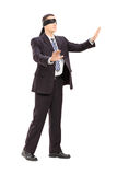 Full length portrait of a blindfolded businessman in suit. Isolated on white background royalty free stock photography