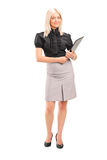 Full length portrait of a blond businesswoman holding a clipboar Stock Photo