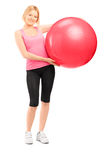Full length portrait of a blond female athlete holding a pilates. Ball isolated against white background Royalty Free Stock Image