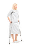 Full length portrait of a blond female patient in hospital gown Royalty Free Stock Photo