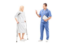 Full length portrait of a blond female patient in hospital gown Stock Photo