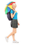 Full length portrait of a blond female student walking with umbr Stock Photography