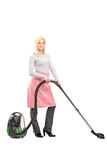 Full length portrait of a blond housewife cleaning with a vacuum Stock Photography