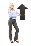 Full length portrait of a blond smiling woman holding a big blac Royalty Free Stock Photos