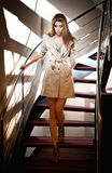 Full-length portrait of blonde woman wearing a coat. Beautiful young woman in coat  descending steps in modern minimalist interior. Full-length portrait of Stock Photography