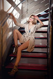Full-length portrait of blonde woman wearing a coat posing provocatively on steps in a modern interior. Beautiful woman in coat. Full-length portrait of blonde royalty free stock image