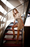 Full-length portrait of blonde woman wearing a coat posing provocatively on steps in a modern interior. Beautiful woman in coat. Full-length portrait of blonde royalty free stock photography