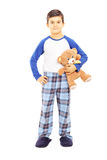 Full length portrait of a boy in pajamas holding teddy bear. Isolated on white background royalty free stock images