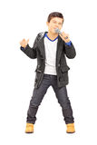 Full length portrait of a boy singing on microphone. Isolated on white background royalty free stock photography