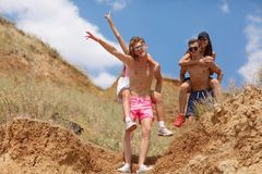 Full-length portrait of boys hold attractive girls in a field on a natural blurred background. Full-length portrait of smiling boys holding girls, vacation near Stock Photography