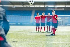 Kids at Football Practice. Full length portrait of boys in junior football team standing in row during practice with captain kicking ball in foreground, copy Stock Photos