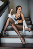 Full-length portrait of brunette woman wearing a white male shirt over black lingerie posing provocatively on steps Royalty Free Stock Image