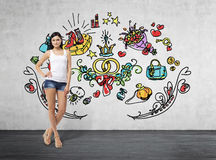 Full length portrait of a brunette woman who is in a white tank top and blue denim shorts. She is dreaming about sopping. Royalty Free Stock Images