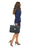 Full length portrait of business woman with briefcase going. Isolated on white. rear view Stock Images