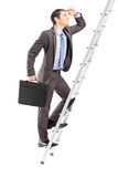 Full length portrait of a businessman with  briefcase climbing a Stock Photography